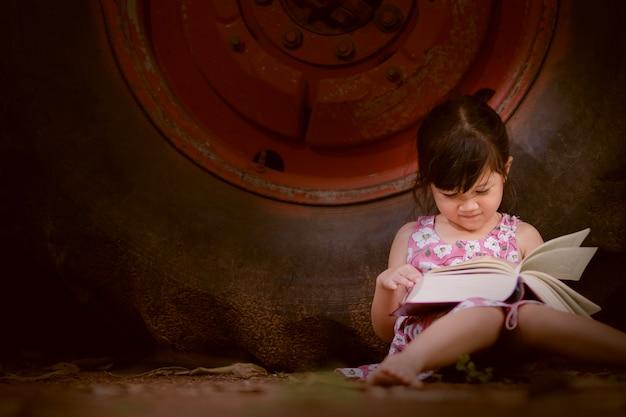 Книга чтения маленькой девочки в свободном времени с счастливым.