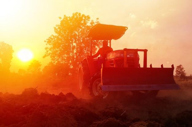 Сельское хозяйство в таиланде, трактор вспахивает почвенное поле