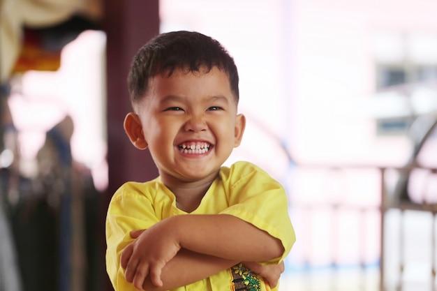 幸せに笑って、彼の手で立っているアジアの少年は交差しました。