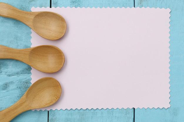 ピンクの紙と青い木のテーブルに木製のスプーン。