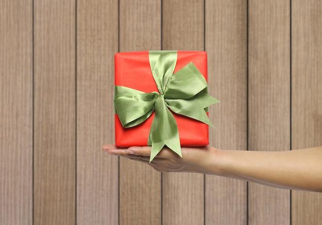 木製の壁の背景に赤いギフトボックスを持っている女性の手。