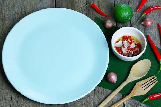 Опорожните зеленый соус плиты и рыб с пряным на таблице еды.