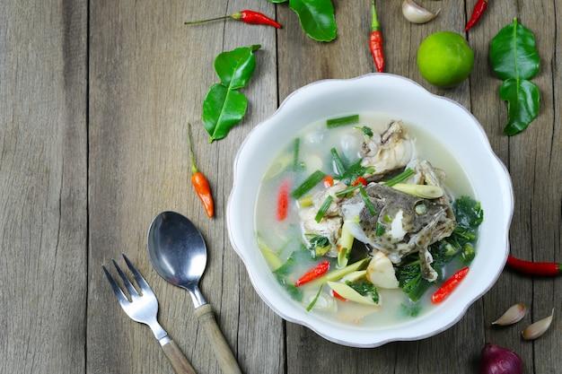 トムヤムハタの魚の木の床のボウルにタイ料理のスパイシースープ。