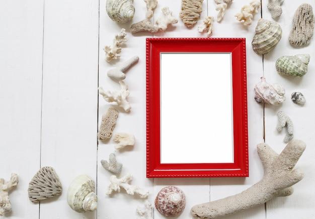 白い木製の床に赤い木製フォトフレームとシェルとサンゴ礁があります。