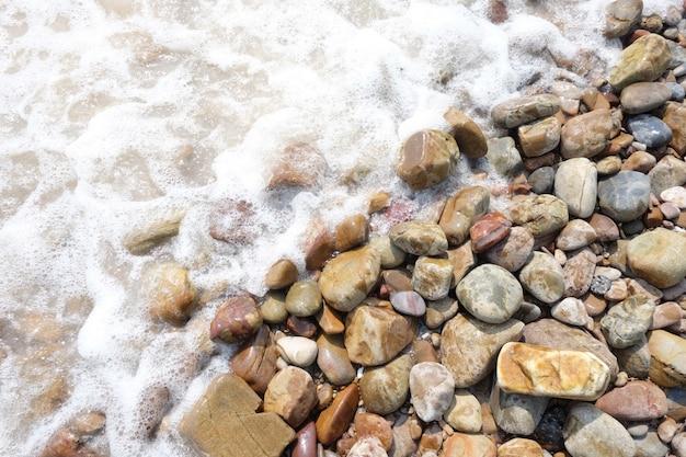 海岸のがれきや小石の多いビーチの背景に波が打ち寄せます。