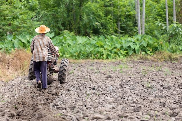 農民は土壌作物を再調整するために制御プッシュカードを働いている。