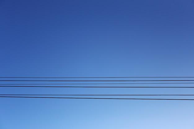 Кабельные провода электрических столбов на фоне голубого неба.