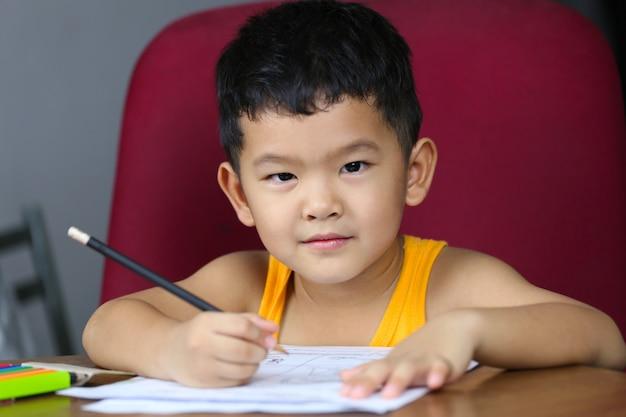 アジアの少年が宿題をしている、自宅で生きて勉強するという概念。