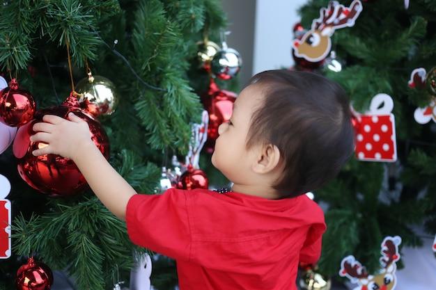 アジアの男の子はクリスマスツリーに興味があります。