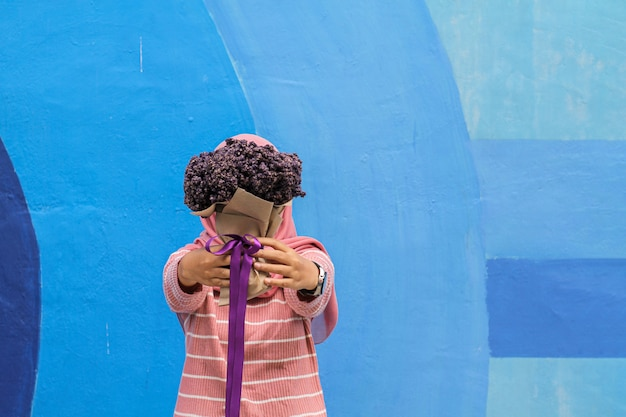 水色の壁に紫の花束を持つ少女
