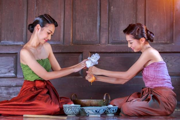 古代タイに身を包んだタイの女性たちはタイのデザートを作るのを助けています