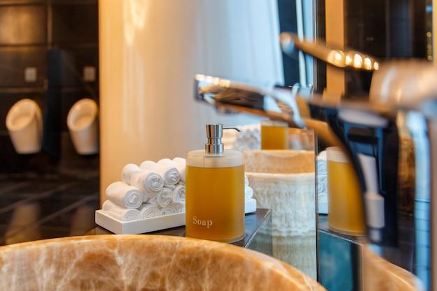 ホテル、ホテルのモダンなバスルームのバスタブに液体石鹸ボトル