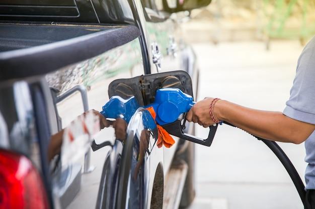 ガソリンスタンドで車内に燃料を追加するには、左手で燃料ノズルを持ちます。