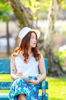 ノートを書くと、木製のベンチに座っていると公園で座っているペンを持つ美しいアジアの女性