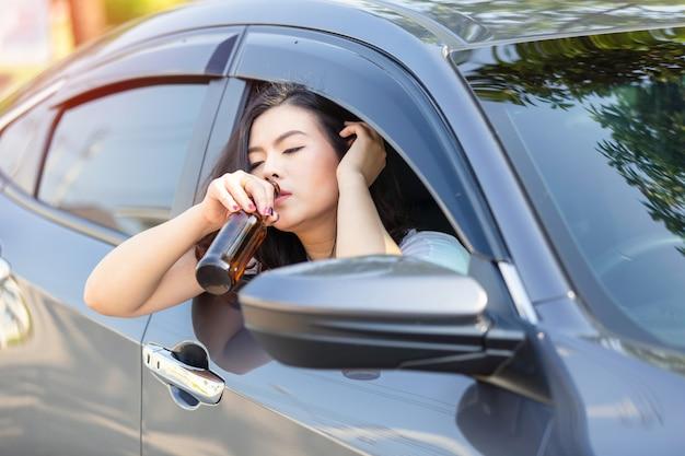 若いアジア女性が車を運転している間ビールを飲みます。