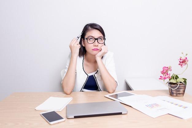 Серьезная азиатская женская исполнительная власть находя идеи пока работающ на ее столе с компьтер-книжкой
