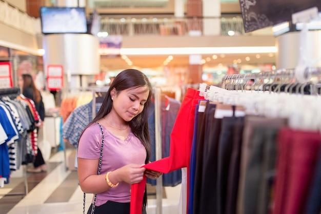 幸せな若いアジア女性がモールや衣料品店でズボンの値札をチェックします。