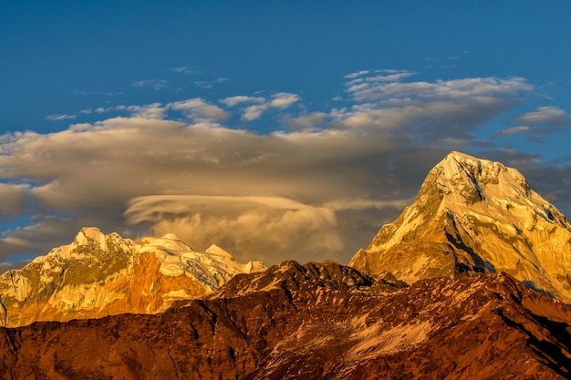 雪の尾根が付いている山の美しい曇り日の出