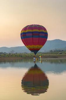 日没時間、チェンライ県、タイの湖の上の熱気色バルーン