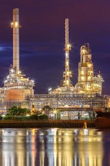 Нефтеперерабатывающий завод вдоль реки в сумерках (бангкок, таиланд)