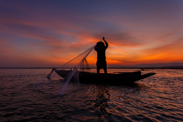 Силуэт традиционных рыбаков, бросая рыболовную сеть озера инле во время восхода солнца, мьянма