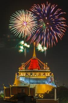 Ярмарка храма золотой горы, храм золотой горы с красной тканью и фейерверк в бангкоке в сумерках.