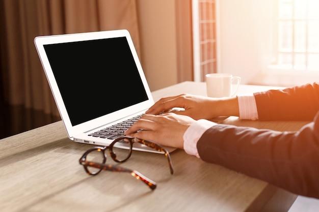 男の手の家の内部の机の上の空白の画面を持つラップトップを使用して。