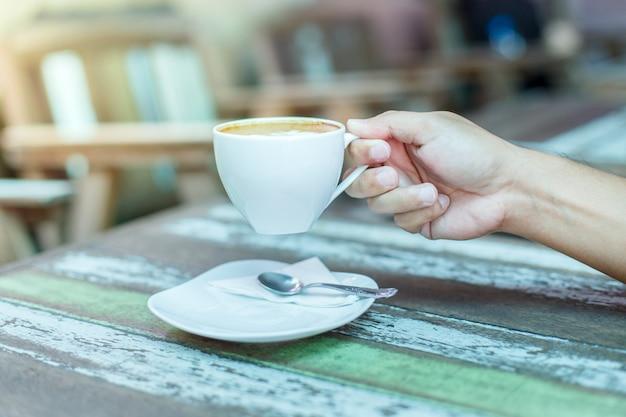 男性の手が木のテーブルに一杯のコーヒーを握る