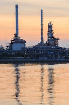 Нефтехимический завод на рассвете с отражением на воде