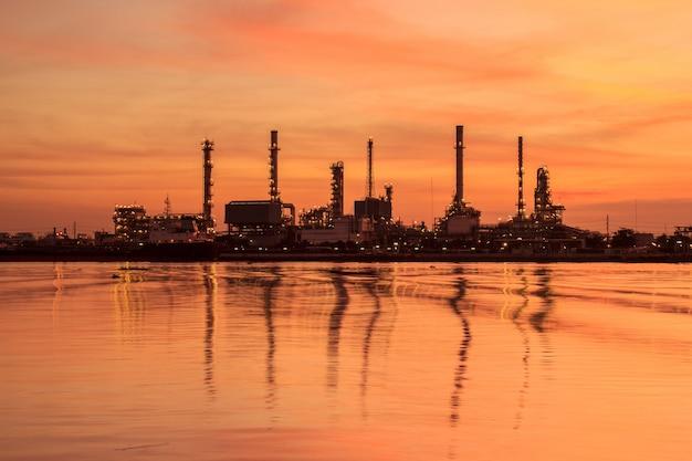 シルエットと日の出の空の石油精製工場