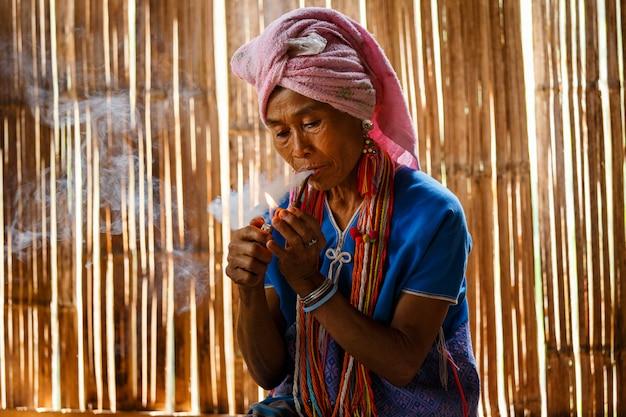 女性のカレンの丘の部族はタイ北部のコテージで伝統的な喫煙タバコパイプ