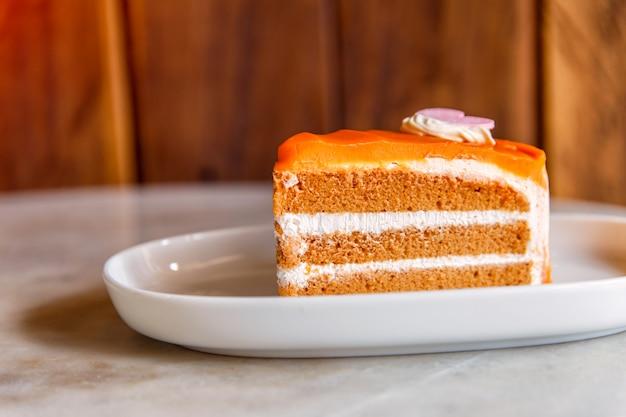 Десерт - сладкий пирог с апельсином на тарелке