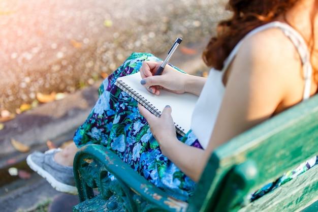 ノートを書くと座っているペンを持つ美しいアジアの女性