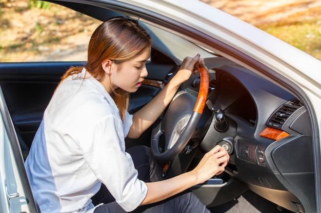 イグニッションキーで車のエンジンを始動させる若いアジア女性