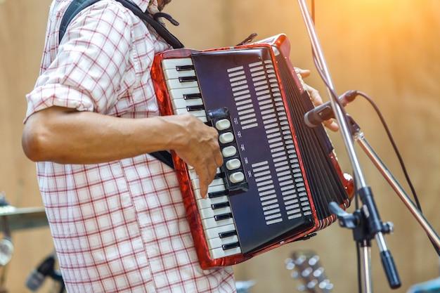 クローズアップミュージシャンがステージ上でアコーディオンを演奏します。