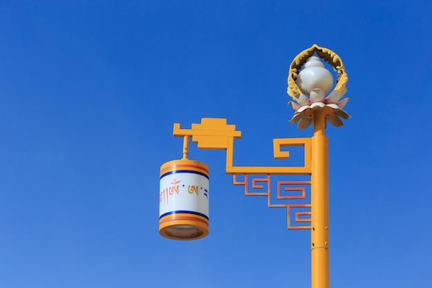 青い空を背景に黄色の街路灯