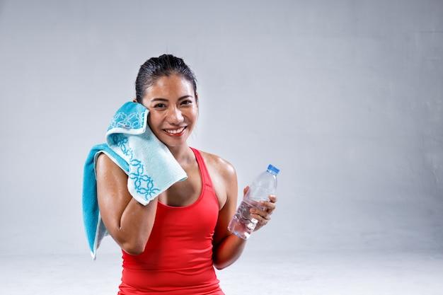 かなりスポーティなインドの女性がコンクリートの背景にヨガのトレーニングの後の水を飲む