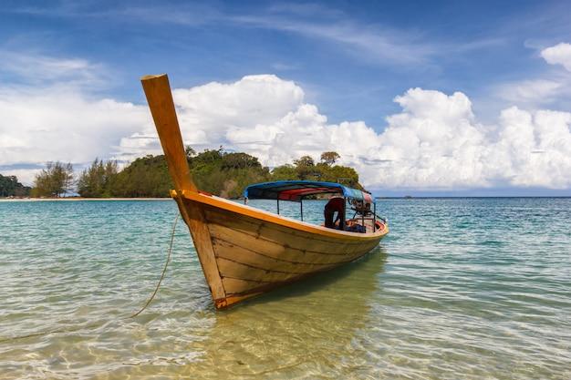 白い砂のビーチとカンカオ島の美しい青い空と青い海に浮かぶ漁師船