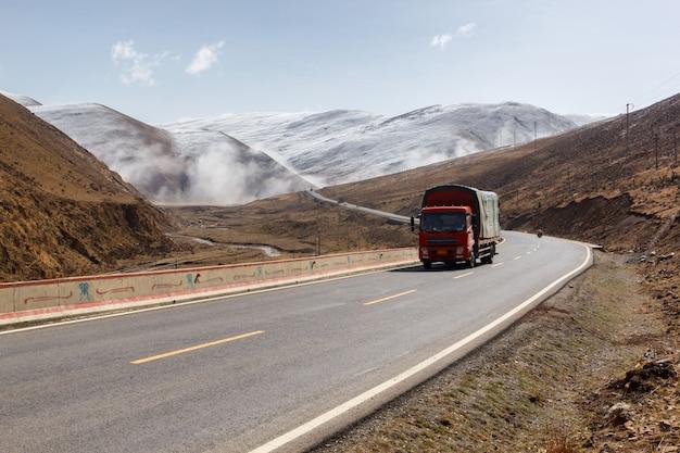 道路上のトラック、雪山四川省中国の下でチベットの美しい冬の道