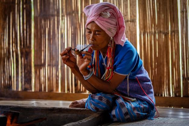 女性カレンの丘の部族はコテージで伝統的な喫煙タバコパイプです。