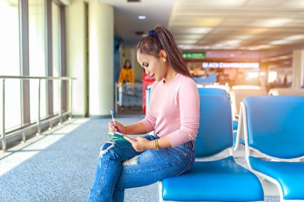 美しい若い観光客は椅子に座っていると国際空港でノートブックにレコード旅行を書く