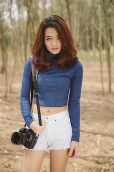 カメラを保持している美しい若いアジア女性の肖像画と公園の上のカメラを見てください。アクションでアジアの女性写真家。