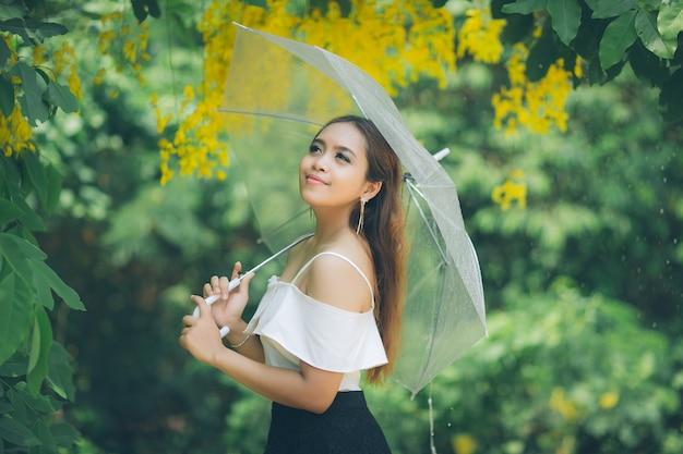 公園で雨の下で傘を持つ美しいアジアの女性の肖像画。
