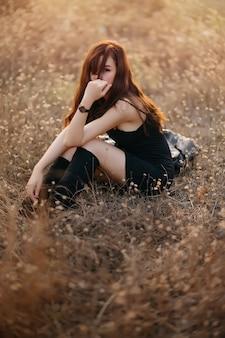 カメラを見てフィールドで屋外に座っている若い陽気なアジア女性