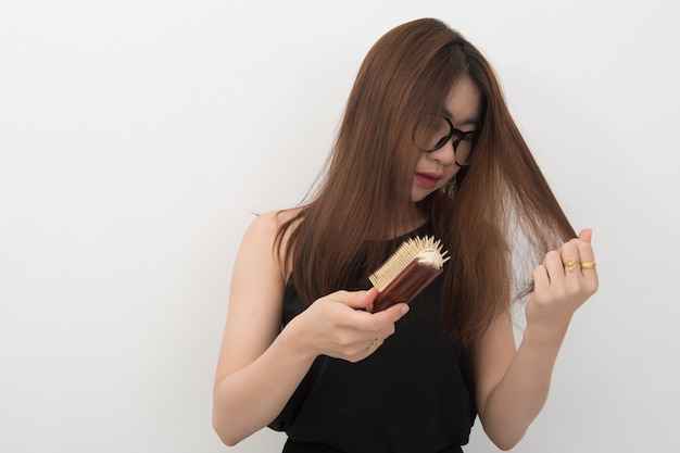 灰色の背景に櫛と問題の髪のアジア女性の長い髪の肖像画。脱毛の概念のためのこの画像。コピースペースがありません。