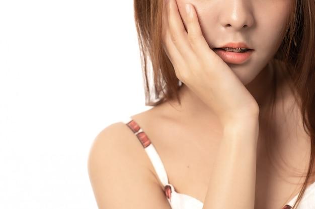 白い背景の上の歯痛の痛みに苦しんでいるアジアの女性、歯痛の女性の肖像画。歯科治療コンセプト;アジアの女性モデルを閉じます。