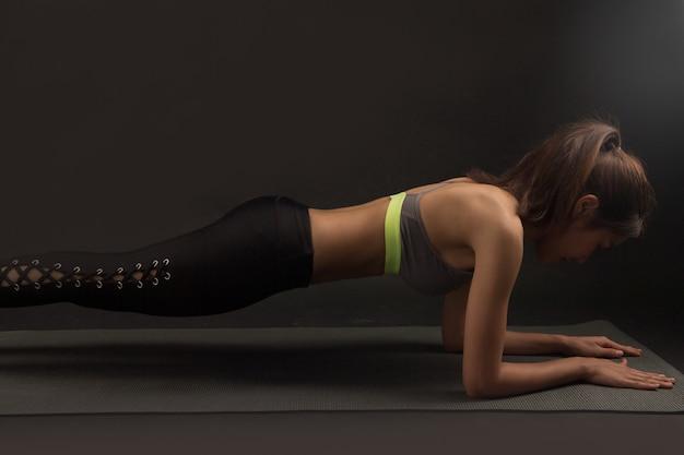 スタジオで黒の背景に板運動をしているスポーツウェアを着ているアジアの若いスポーツ女性。タイの女の子の運動、ヘルスケアの概念。