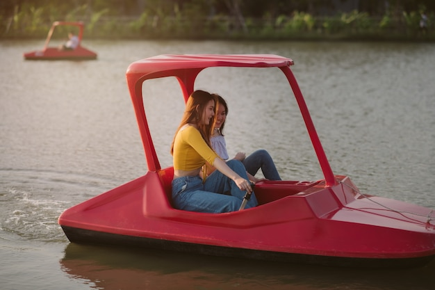 Портрет двух женщин расслабиться на байдарке; дружеский разговор; счастливая женщина на водном велосипеде на воде в парке.