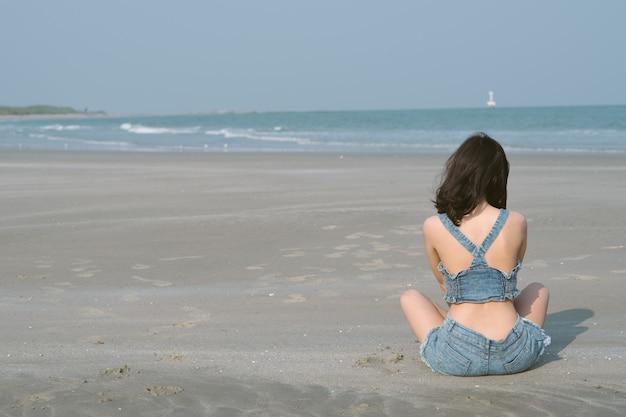 Задний взгляд портрета азиатской женщины сидя на тропическом пляже в концепции образа жизни таиланда, счастливых и беспечальных.