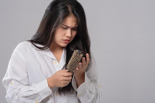 櫛と白い背景の上の問題の髪のアジアの女性の長い髪の肖像画。この画像は脱毛のコンセプトです。コピースペースから解放されます。